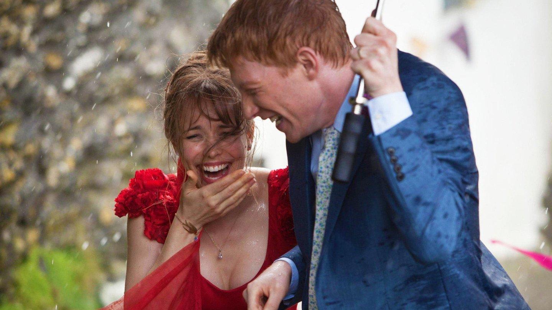 Homem e mulher sorrindo enquanto dividem guarda chuva / Cena do filme Questão de Tempo