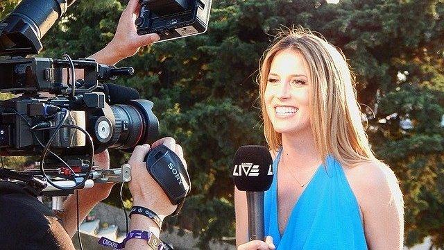 Mulher sorrindo e segurando microfone em frente a câmeras
