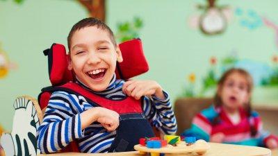 Criança com deficiência sorrindo em cadeira de rodas