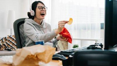 Mulher dando risada enquanto come salgadinho em frente de computador