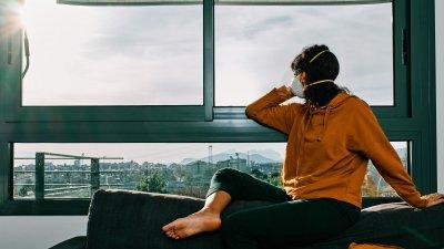 Mulher sentada em um sofá ao lado de uma janela usando máscara de proteção