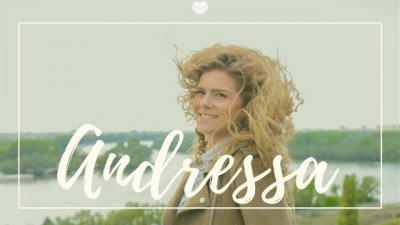 Nome Andressa escrito em branco sobre imagem de mulher jovem, ao ar livre, com os cabelos ao vento