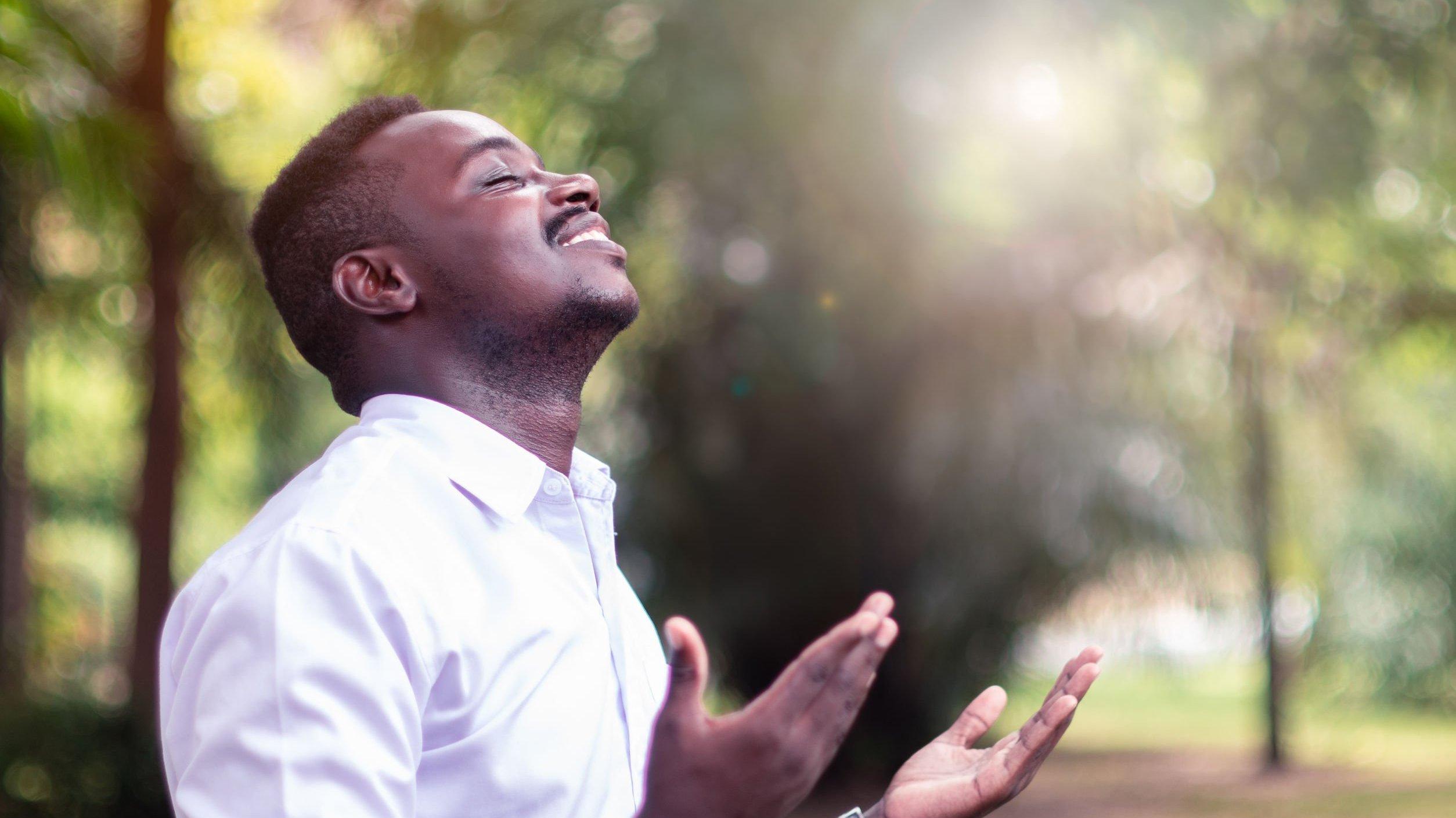 Homem negro, de olhos fechados, sorrindo, com as mãos estendidas