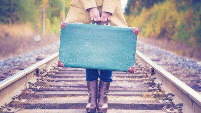 Mulher segurando mala de viajem em trilho de trem
