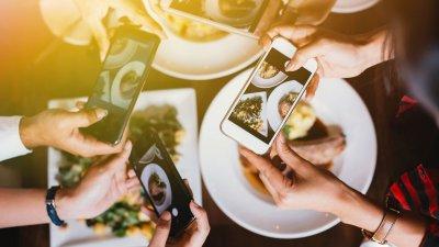 Mãos segurando celulares com câmeras ligadas apontando para a comida na mesa.