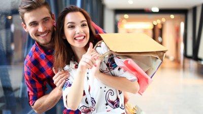 Homem e mulher sorrindo, segurando sacolas, em corredor de shopping