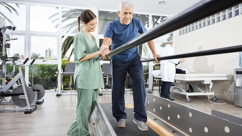 Fisioterapeuta ajudando idoso a caminhar