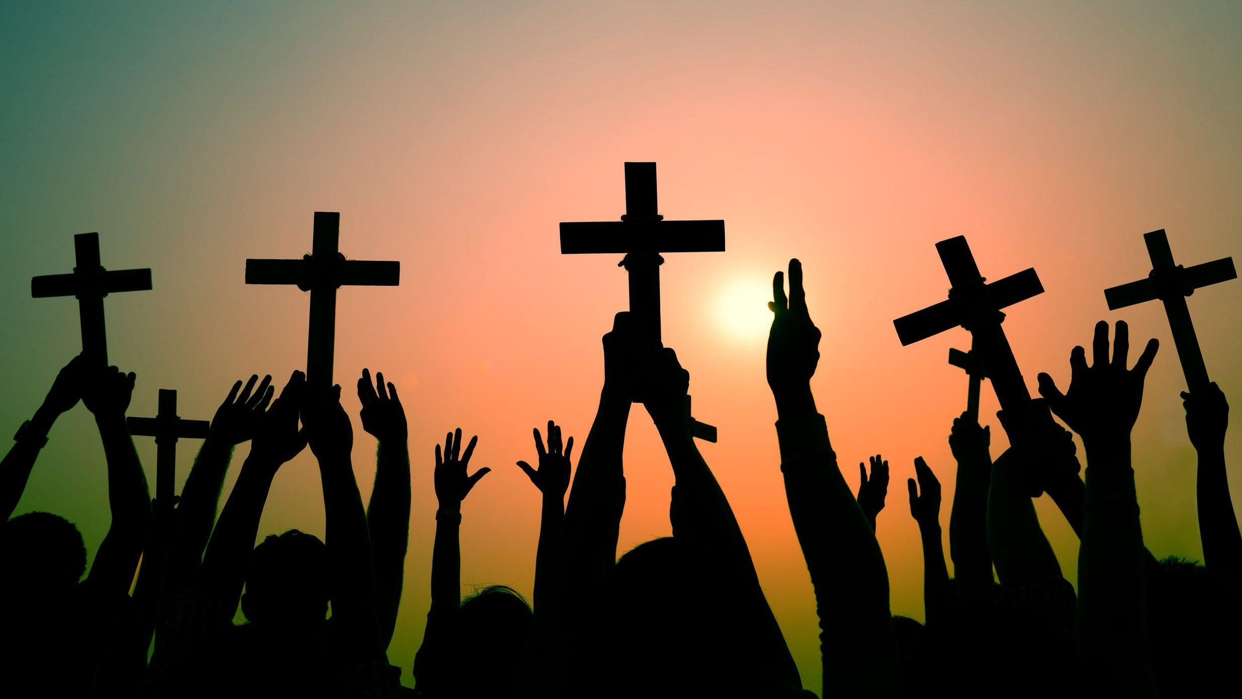 Mãos segurando cruzes ao alto.