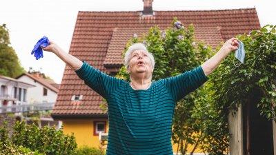 Mulher idosa respira aliviada com os braços abertos enquanto segura uma máscara e luvas de proteção