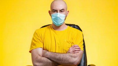 Homem sentado de braços cruzados e uma sobrancelha levantada enquanto usa máscara de proteção