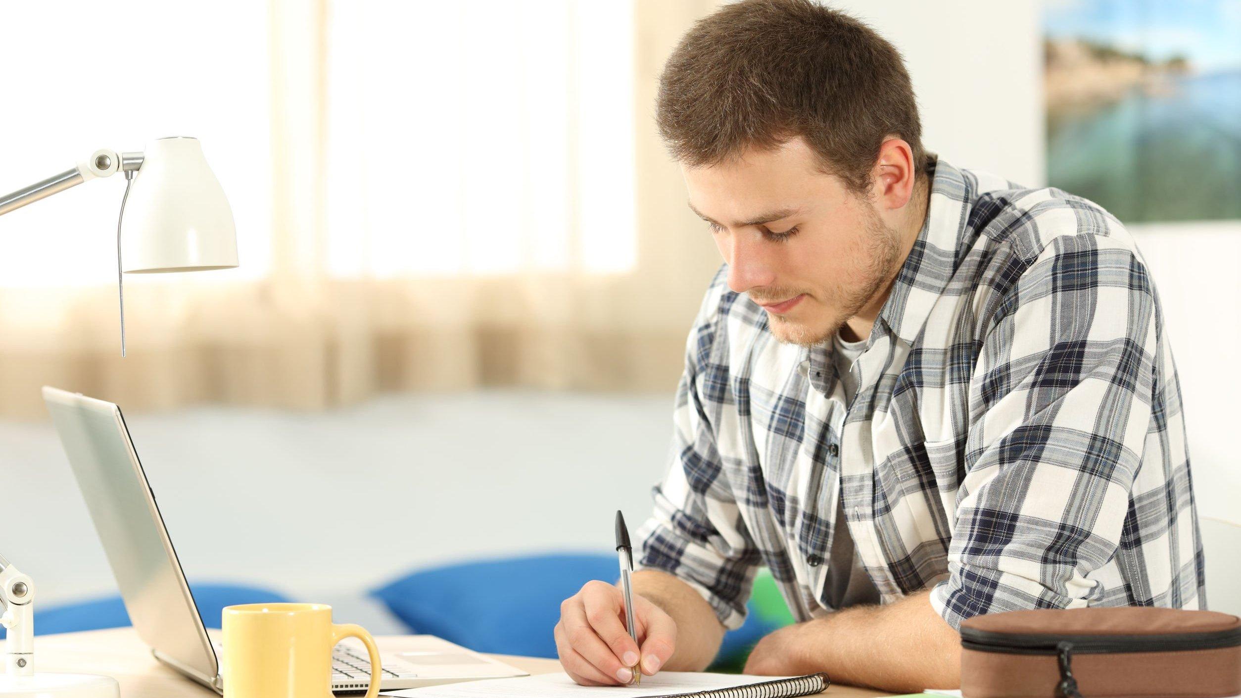 Homem estudando em uma mesa, em casa