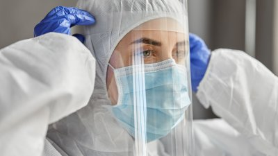 Profissional da saúde colocando seu material de proteção facial