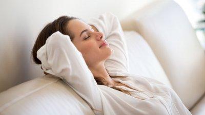 Mulher branca com a cabeça encostada no sofá e expressão calma