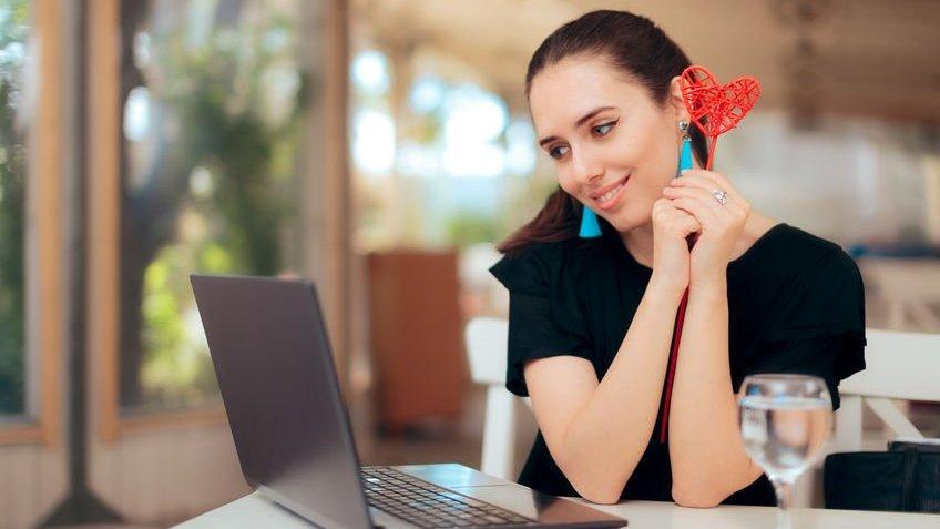 Mulher em casa usando notebook com olhar apaixonado