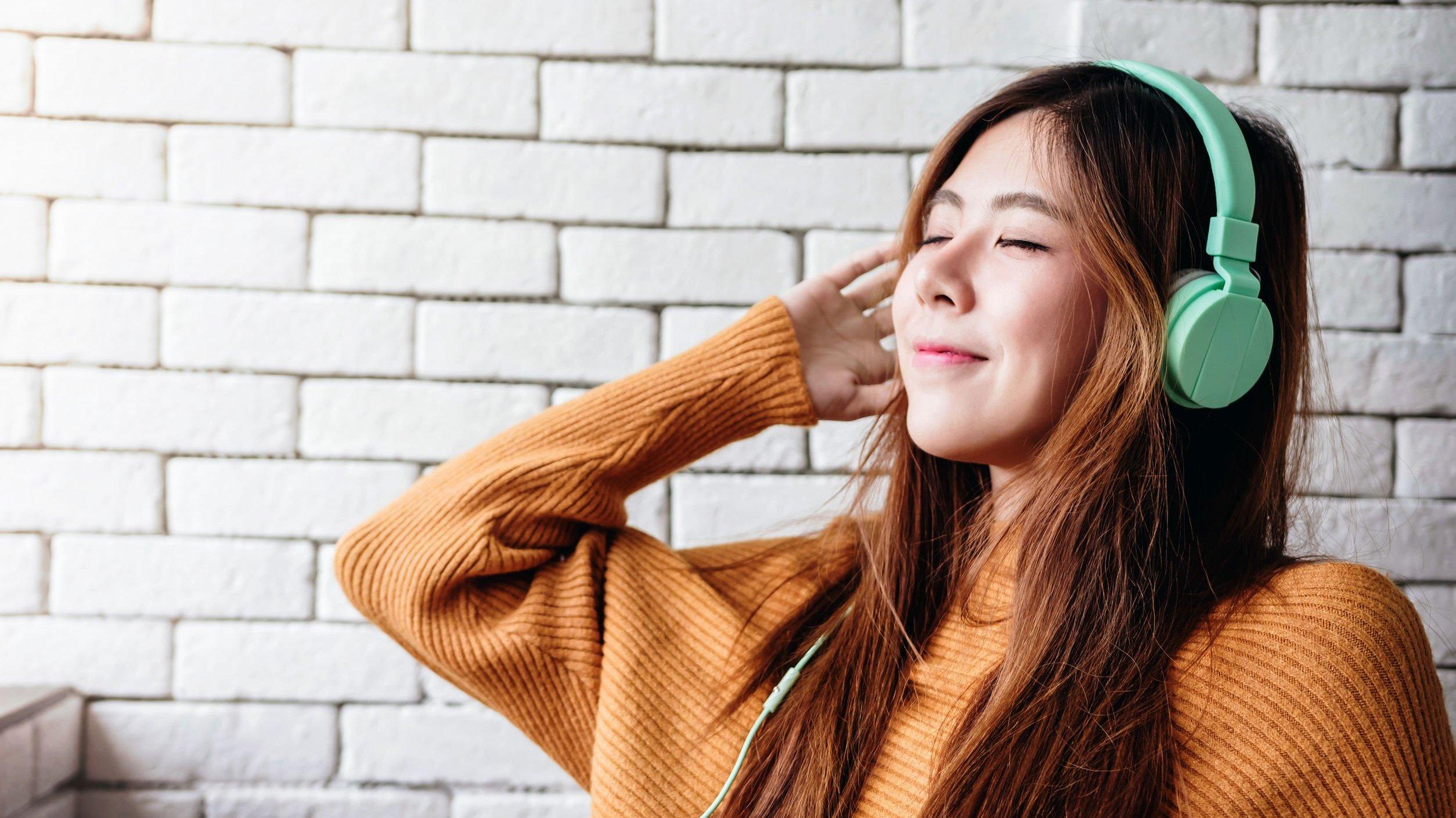 Mulher de olhos fechados ouvindo música e sorrindo.