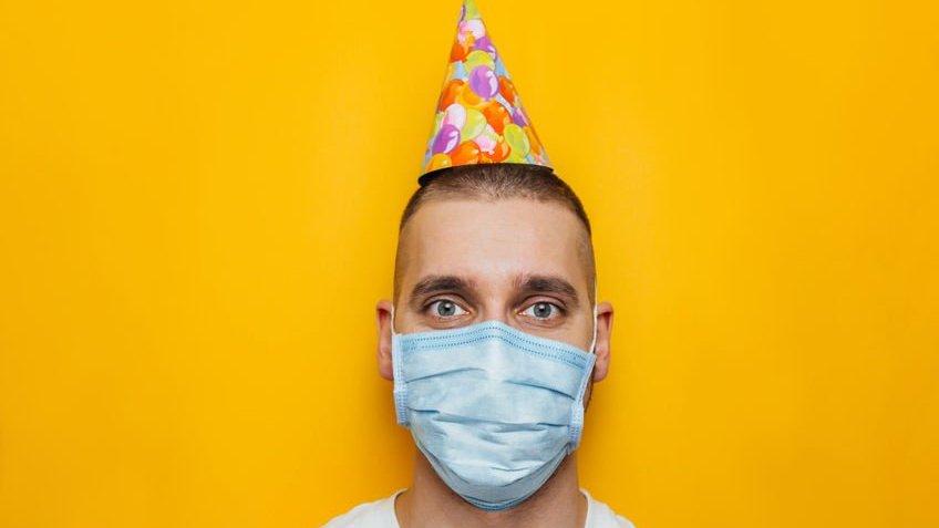 Homem usando chapeuzinho de aniversário e máscara