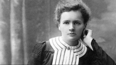 Marie Curie olhando para o lado apoiando seu queixo na mão