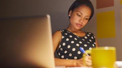 Mulher em seu escritório fazendo anotações em uma folha com seu notebook aberto ao lado