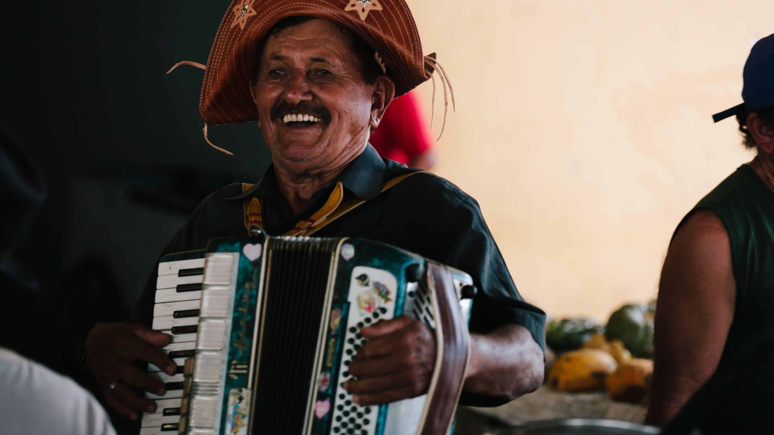 Homem nordestino sorrindo e tocando sanfona.