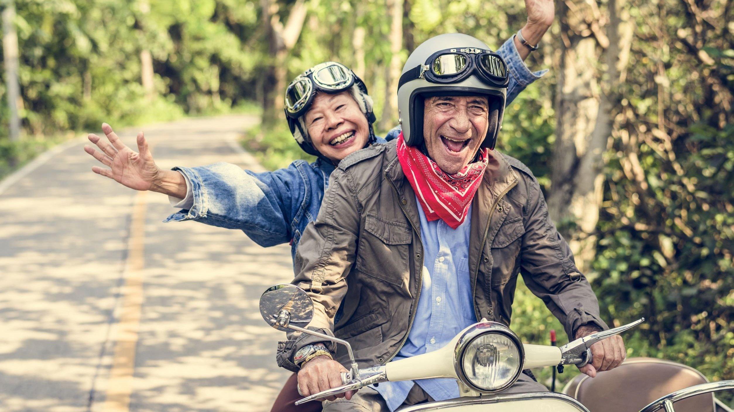 Idosos andando de motocicleta, sorrindo.
