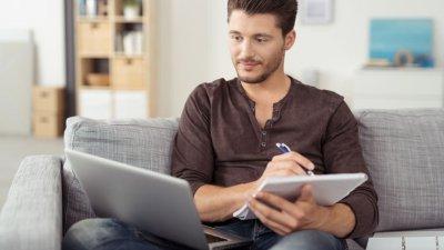 Garoto estudando no sofá de casa com caderno e notebook