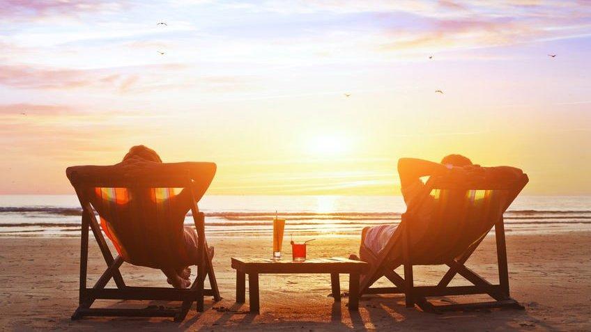 Duas pessoas sentadas em cadeiras de praia olhando pôr-do-sol da areia