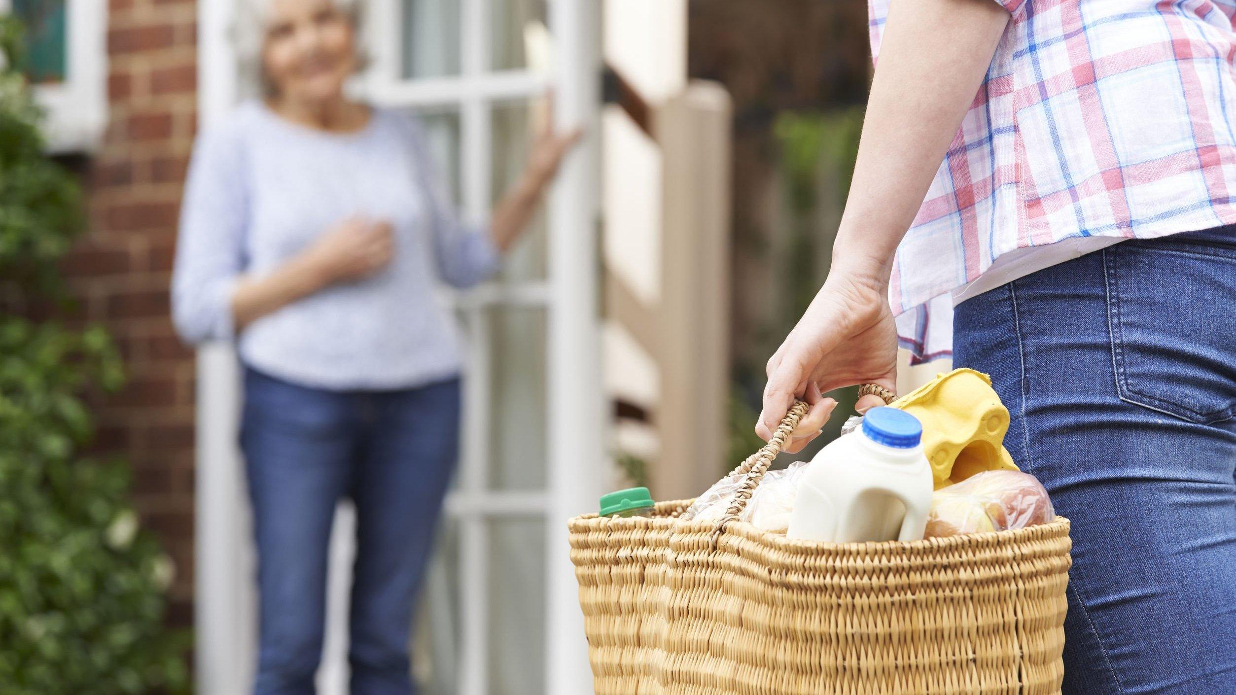 Homem segurando sacola com compras para senhora.