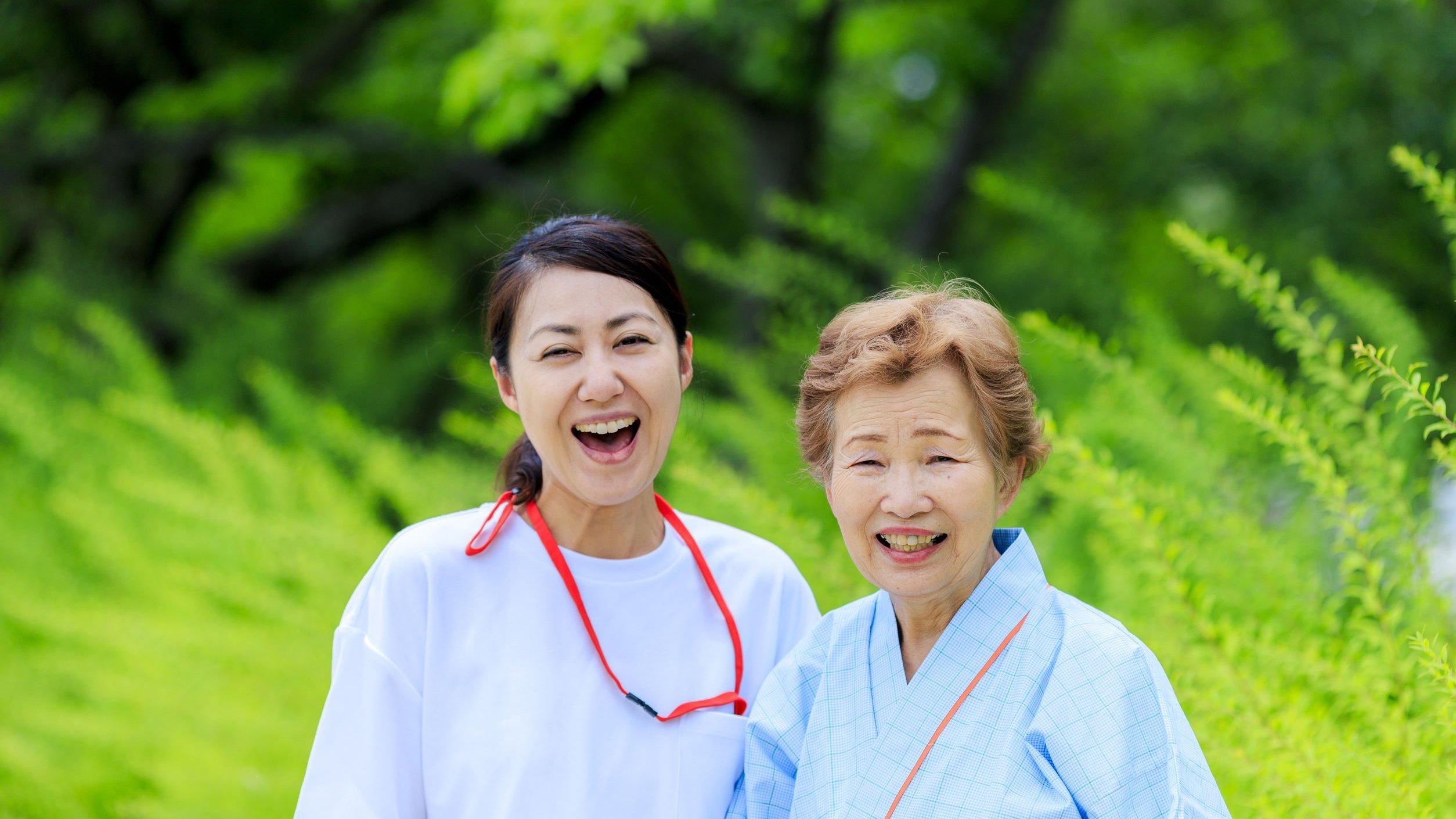 Cuidadora e idosa em foto sorrindo.