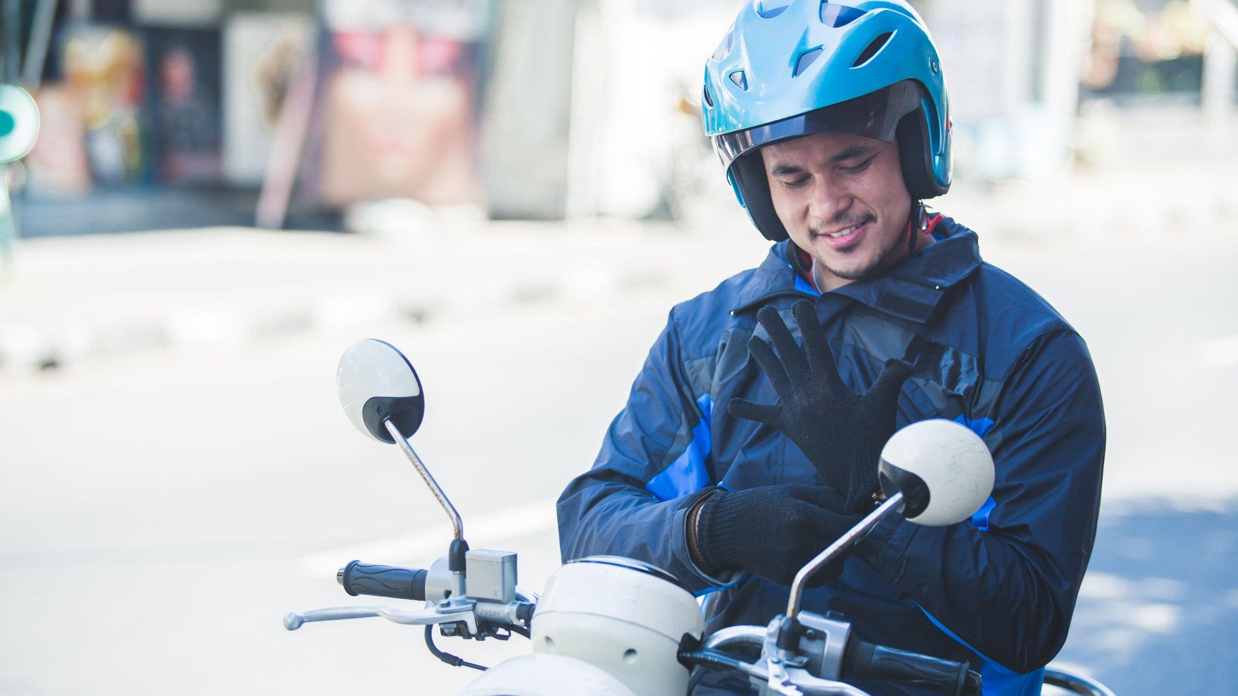 Homem em moto,  vestindo par de luvas