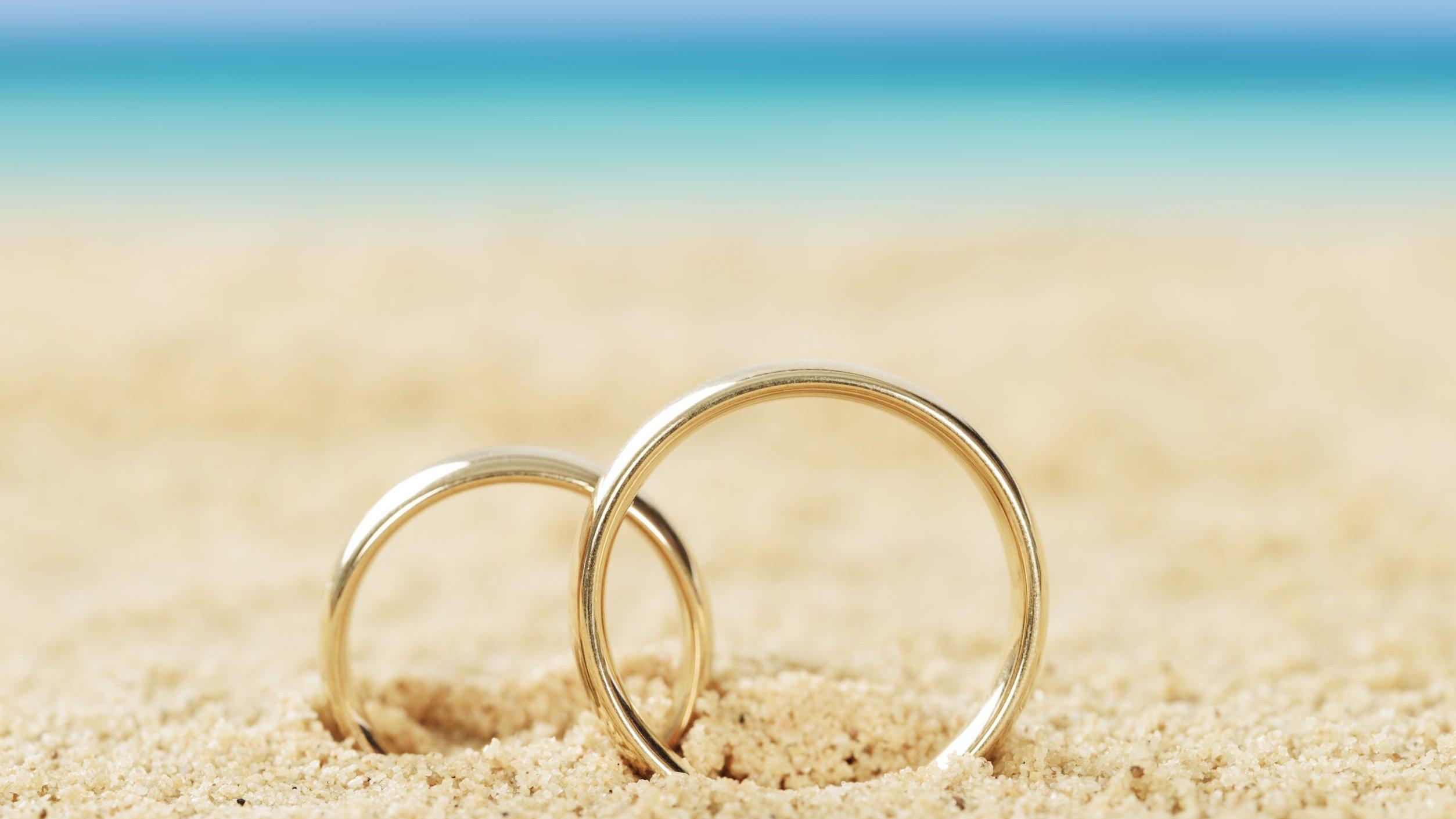 Alianças douradas na areia de uma praia