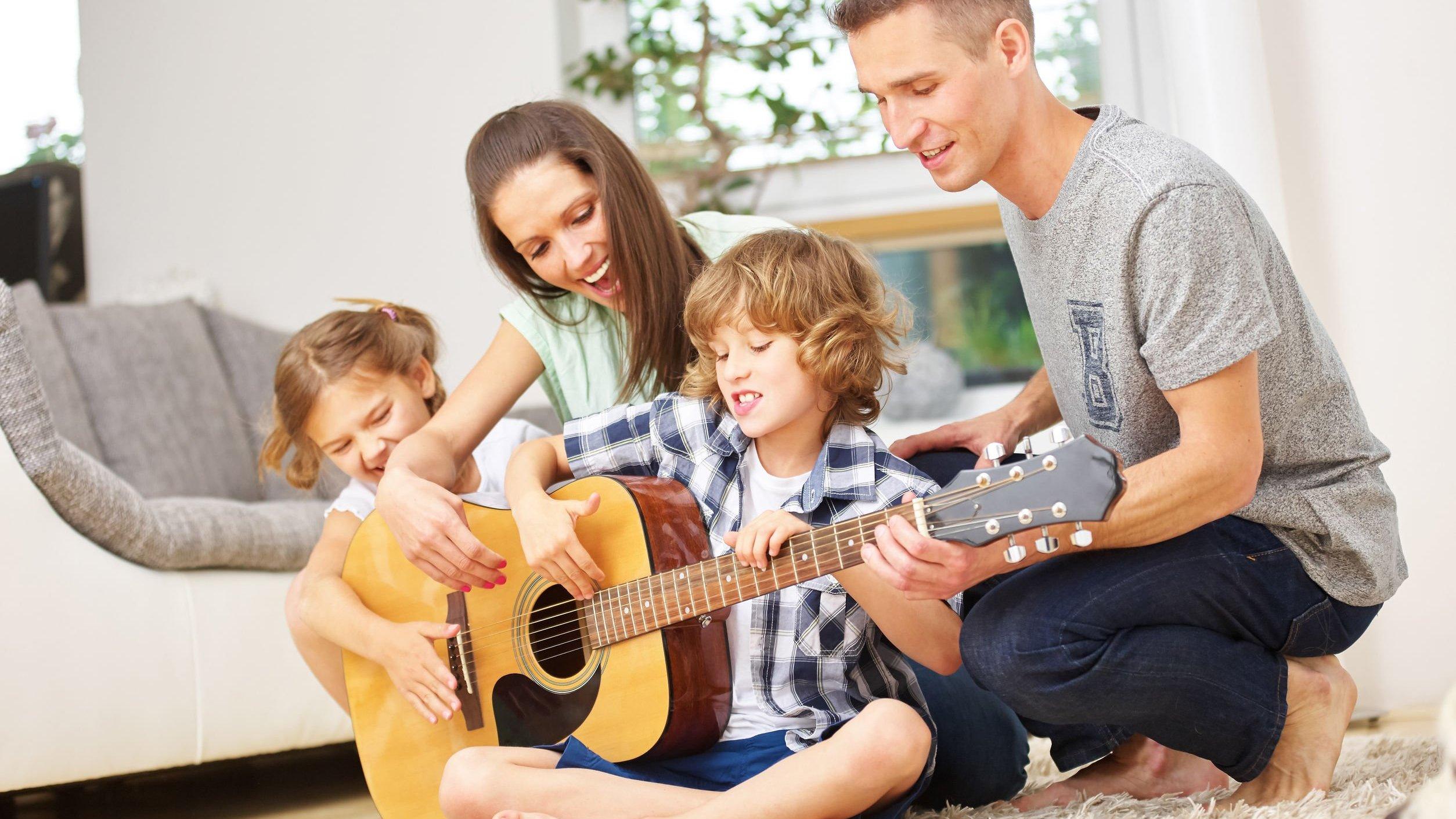 Família reunida tocando violão.