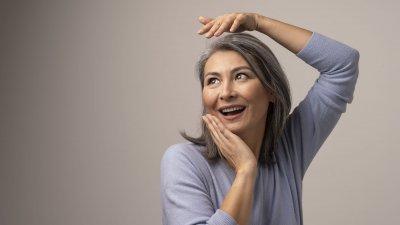 Mulher de cabelos grisalhos sorrindo.