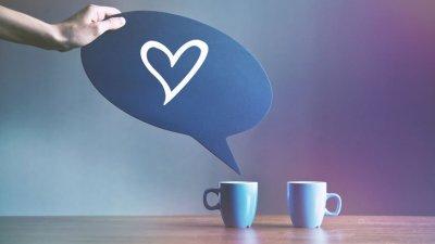 Pessoa segurando um balão de fala com um coração, ao lado de duas canecas.