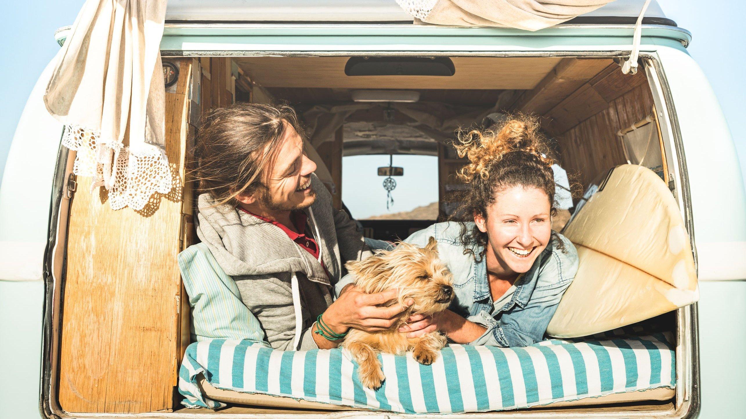 Casal branco deitado dentro de uma Kombi com um cachorro, expressões sorridentes