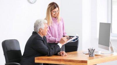 Mulher e homem brancos em escritório sorrindo.