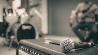 Microfone em cima de amplificador e bateria ao fundo