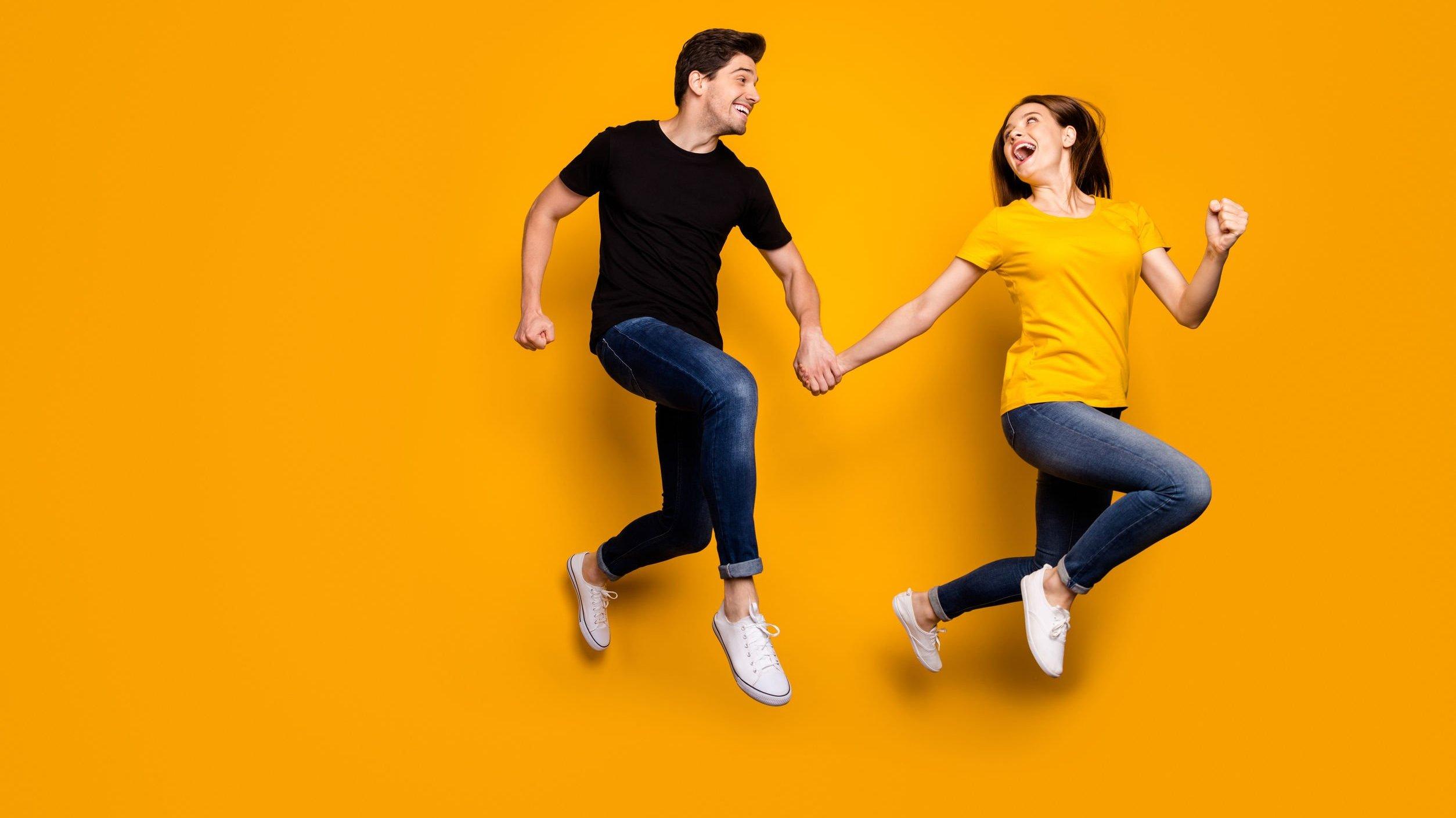 Homem e mulher pulando de mãos dadas e sorrindo