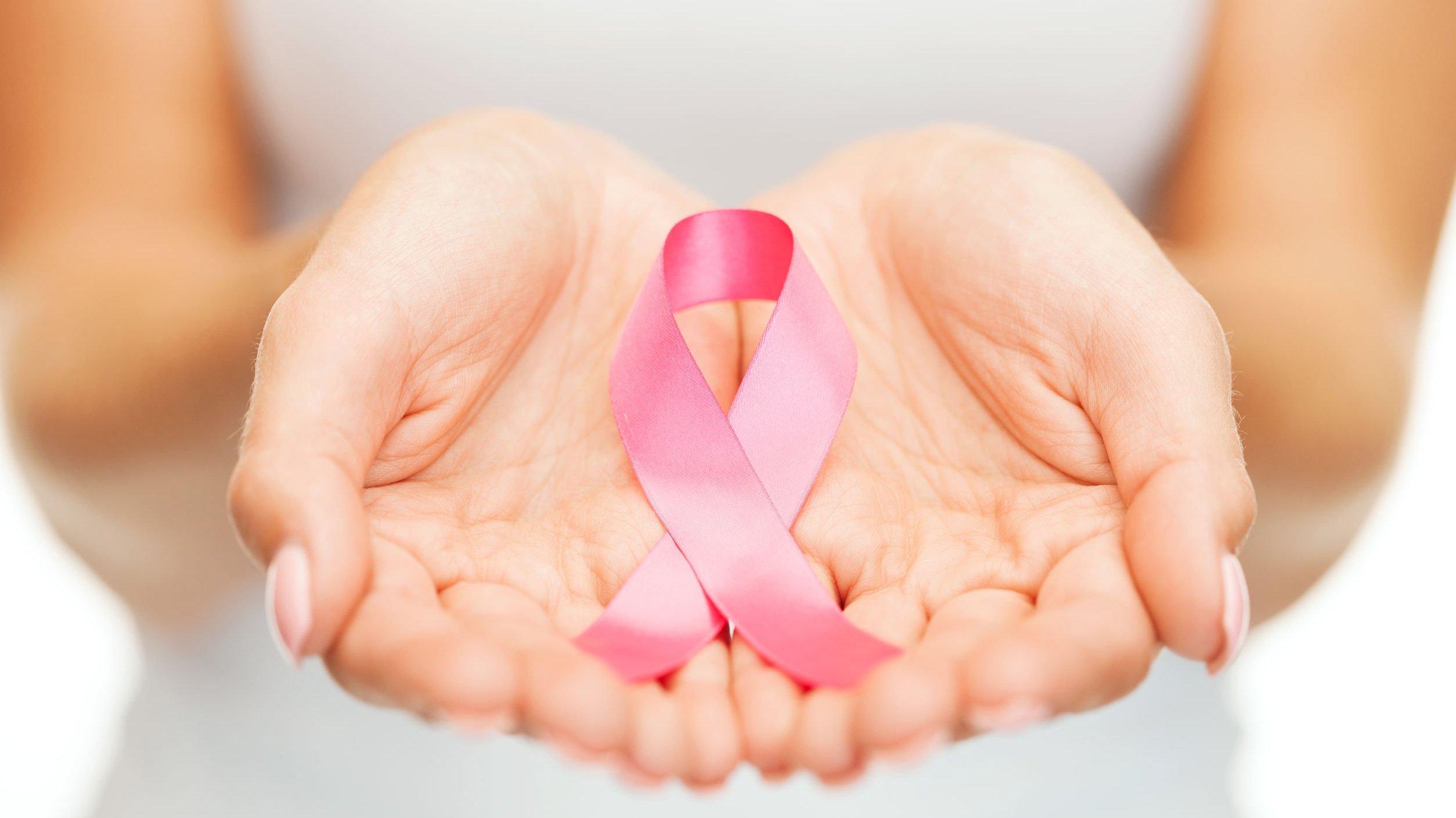 Mulher segurando fita rosa nas mãos.