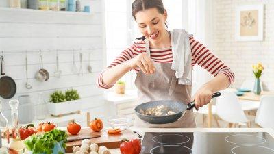 Dona de casa sorri enquanto cozinha
