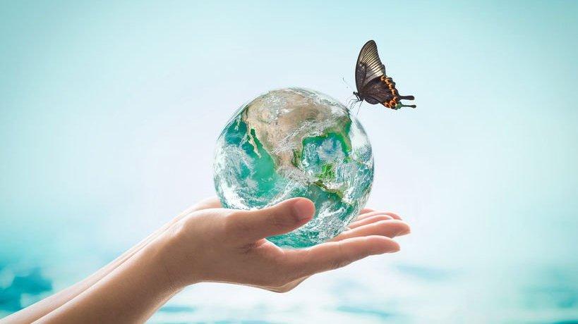 Mão segurando planeta e borboleta pousando