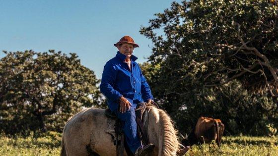 Homem sorrindo montado em um cavalo