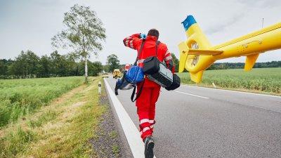 Socorrista com roupas vermelhas com bolsas correndo no asfalto.