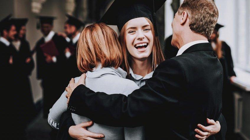 Menina abraçando os pais na formatura