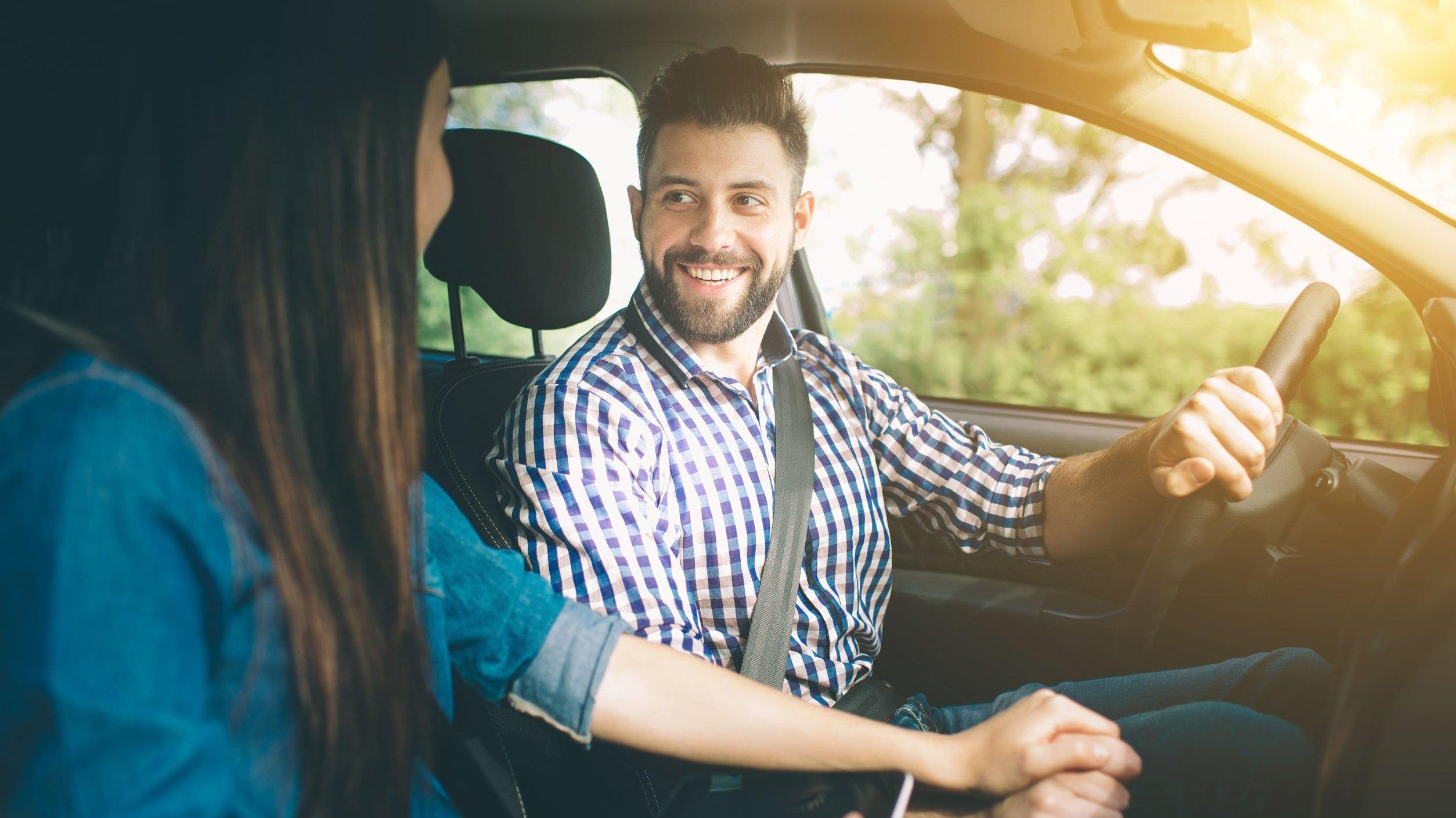 Homem e mulher em carro, sorrindo. Homem usando sinto de segurança.
