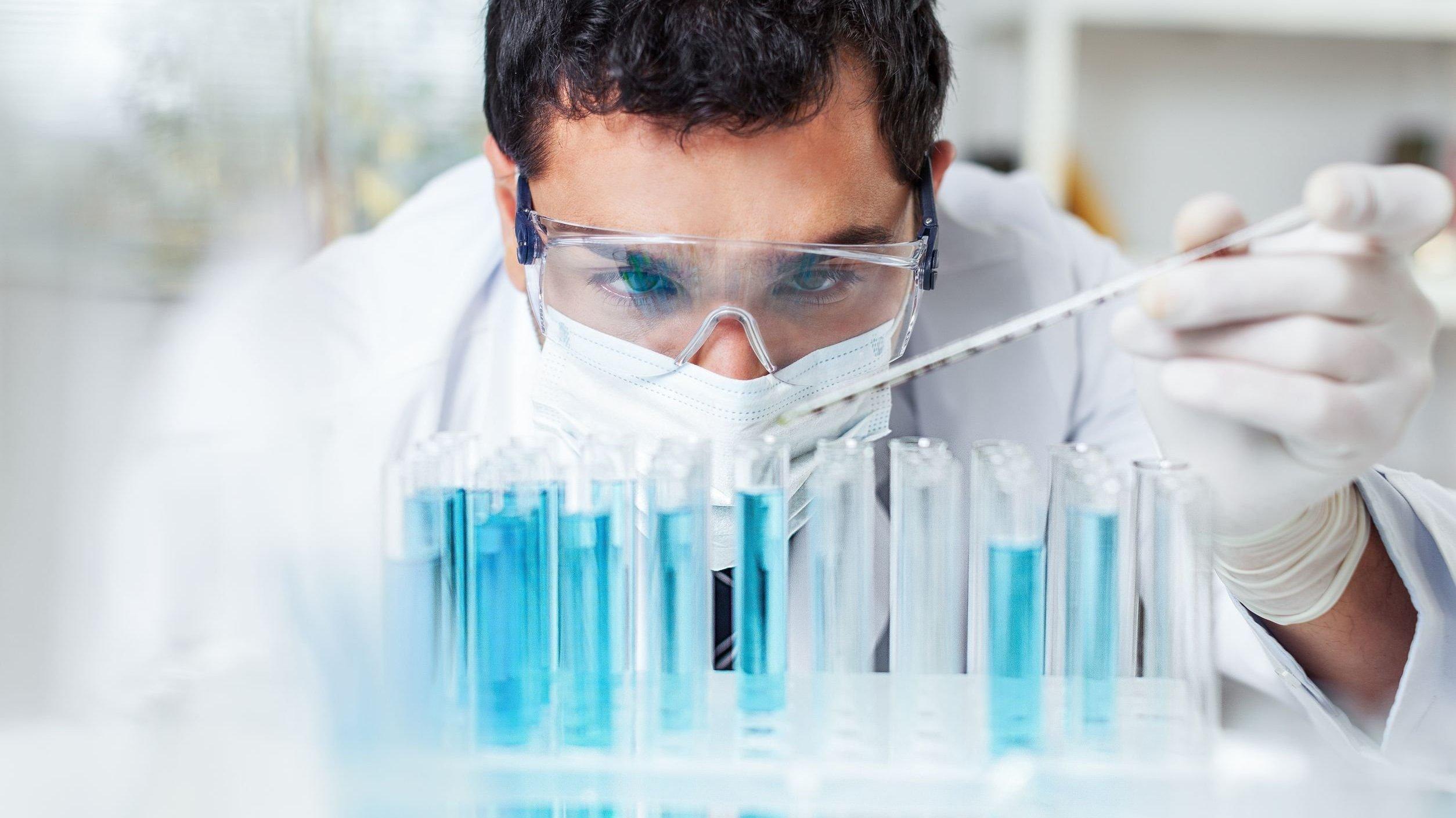 Pesquisador mexendo em tubos de ensaio