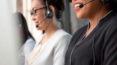 Duas mulheres do telemarketing falando com seus fones