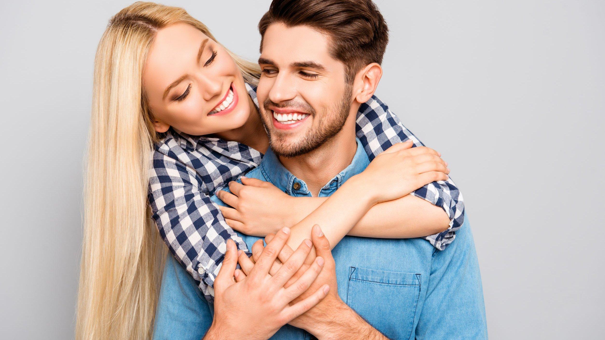 Casal se abraçando e sorrindo.
