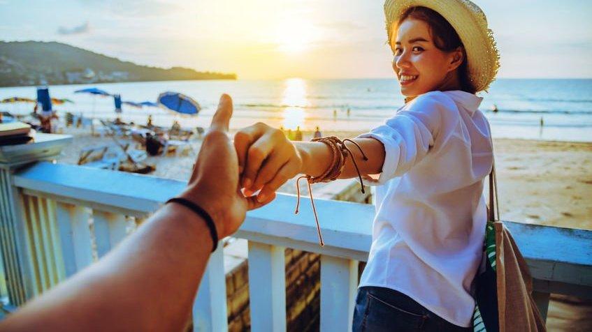 Mulher na praia segurando a mão de amiga