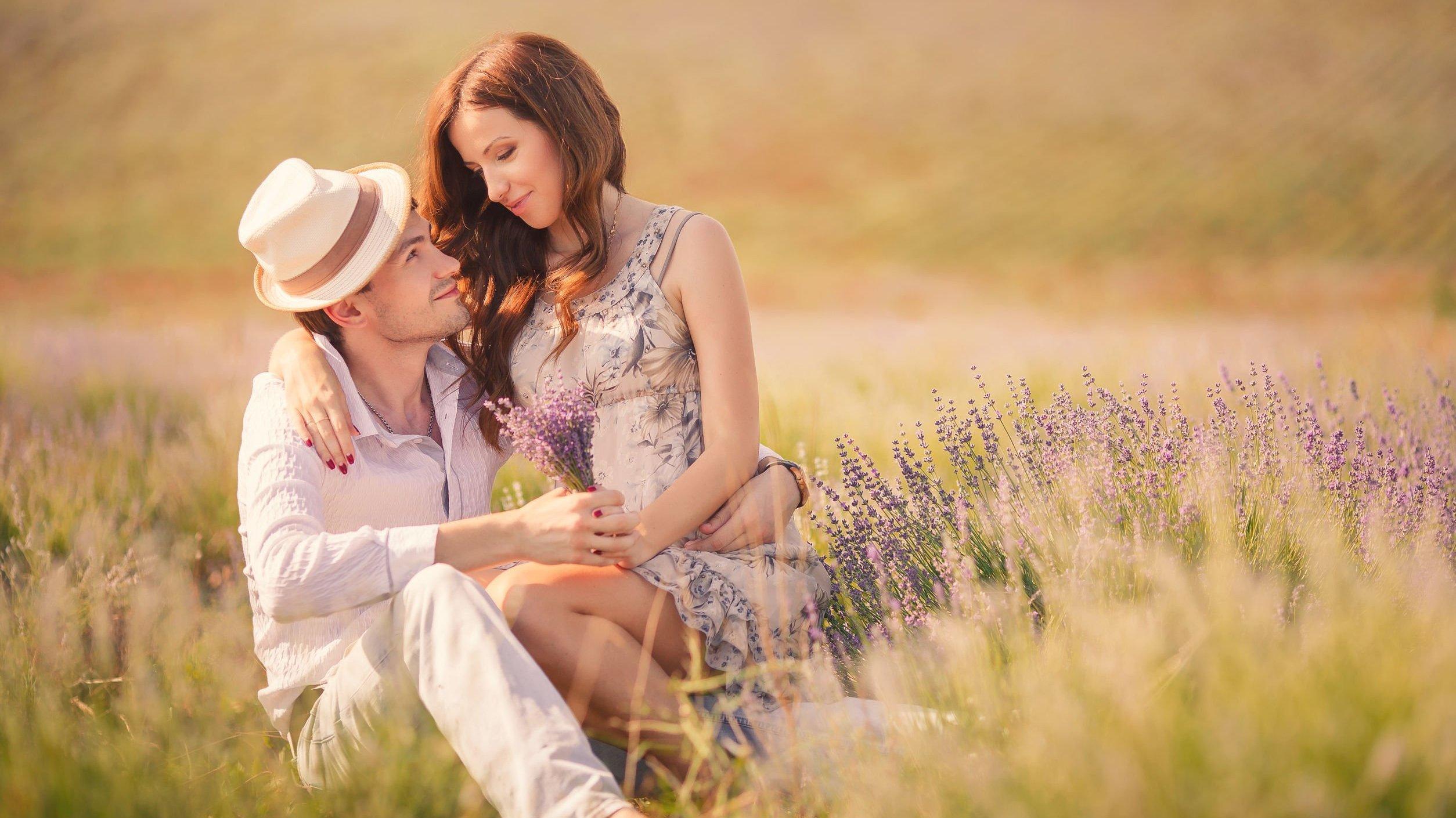 Casal sentado em campo, se olhando e sorrindo.