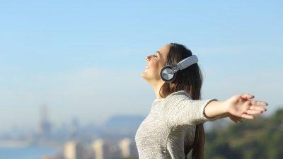 Mulher de braços abertos, sorrindo e com fone de ouvidos, ouvindo música.